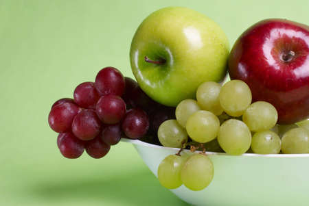 Fresh fruits. Green and red apples and grapes on plate on green background. Stock Photo