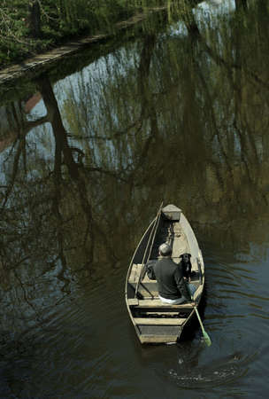 Man and dog canoeing down a peaceful river. Stock Photo
