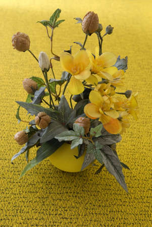 Artificial flowers ona table in yellow flower-pot.