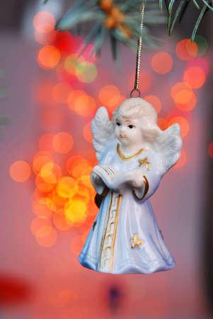 Christmas ball - angel on tree and Xmas light background. Stock Photo