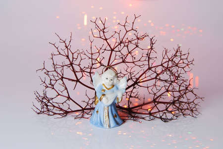Christmas ball - angel on background of sprig tree and Xmas light.