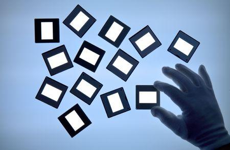 diapositivas en una mesa de luz, espacio de libre copia, con mano enguantada Foto de archivo