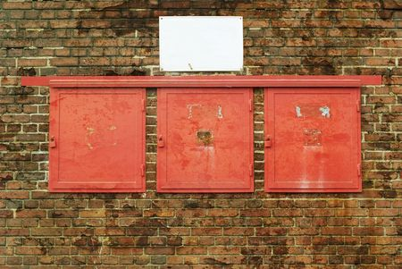 Red clacks and a empty sign on a grungy brick wall , free copy space photo