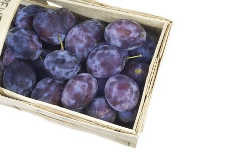 Ripe blue plums in a basket, isolated on white background photo