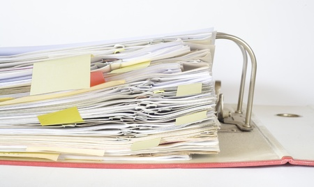 disorganization: open file folder with paper clips, close up