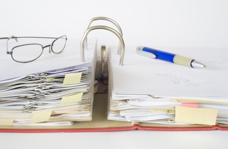 disorganization: open file folder with spectacles and pen