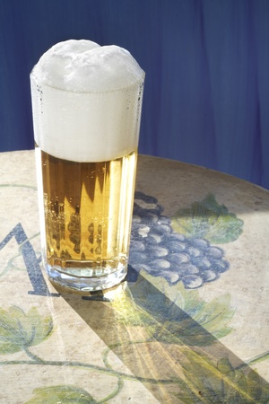 Glass of beer, sunlight, old table, blue background Stock Photo - 12931795