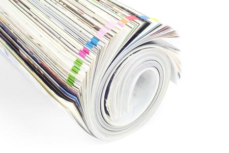 Rolled up magazine, newspaper, with colorful index, white background photo