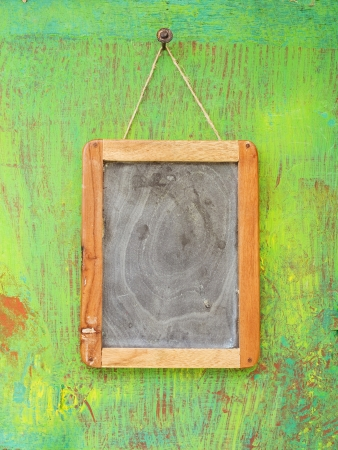 scuff: old blackboard hanging on painted wooden wall, free copy space
