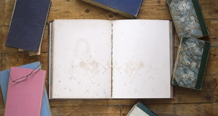 old books, one opened, with blank pages on wooden table photo