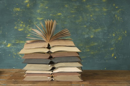 stack of open books on green background, free copy space photo