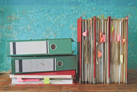 row of file folders with messy documents