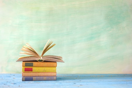 stack of books, one open, grungy background,free copy space Stockfoto