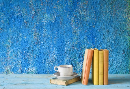 vintage books with a cup of coffee, grungy background, free copy space  Standard-Bild