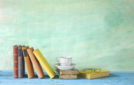 vintage books with coffee cup, spectacles, grungy background, free copy space