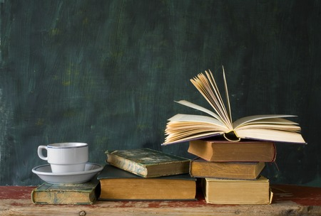 school desk: stack of books, open book, cup of coffee, chalk board, free copy space