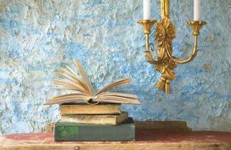candleholder: stack of old books, candleholder, free copy space