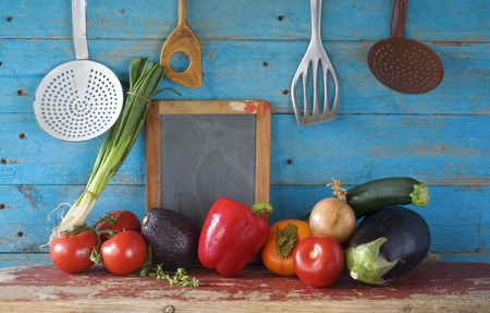 country kitchen: various vegetables, kitchen utensils, blackboard, free copy space