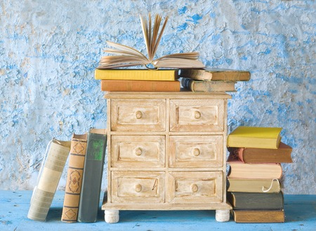 chest of drawers: stacks of books and a small chest of drawers, free copy space