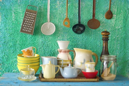 collection of vintage kitchenware, green wall  background photo