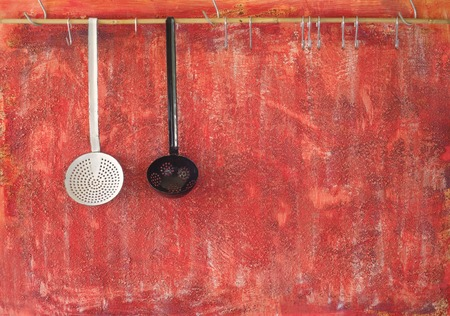 cooking implement: Cooking utensils against rustic old red wall; free copy space
