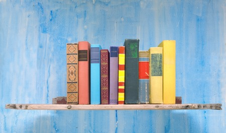 book spine: multicolored books on an old bookshelf free copy space