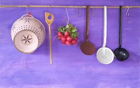 hanging vintage kitchen utensils and a bunch of radish cooking concept copyspace