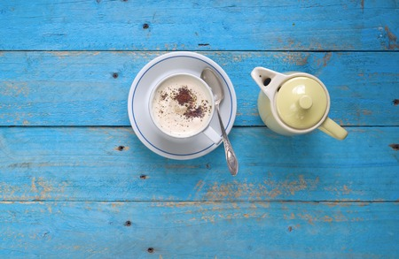 taza cafe: cappuccino italiano y una cafetera en la mesa azul, copia espacio libre