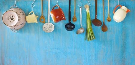 utencilios de cocina: colgar utensilios de cocina de época y un manojo de cebollas verdes, el concepto de la cocina, el espacio de copia Foto de archivo