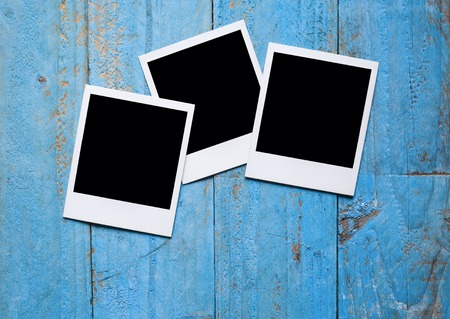 photo paper: Blank instant photo frames on old blue wooden background Stock Photo