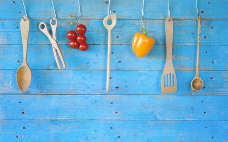cooking utensils: old wooden kitchen utensils and vegetables on rustic kitchen wall, good copy space Stock Photo