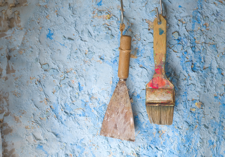 scraper: old scraper and paintbrush, on an old plastered wall, renovating concept