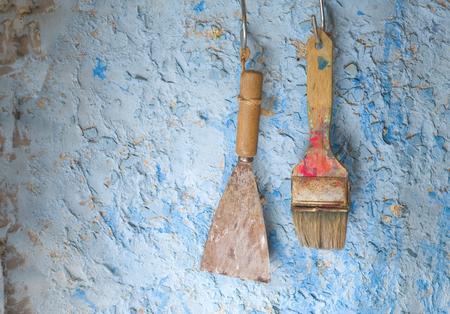 brocha de pintura: vieja espátula y pincel, en una vieja pared enyesada, el concepto de la renovación