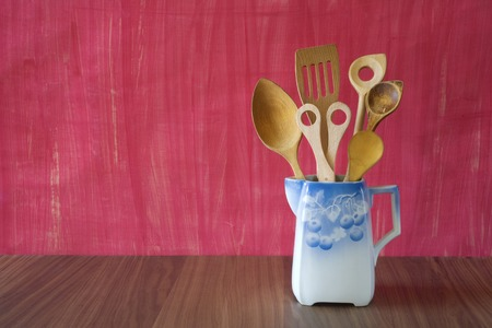rustic kitchen: rustic kitchen utensils in an old jug, good copy space on the background Stock Photo