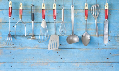 vintage kitchen utensils on blue rustic wall, free copy space