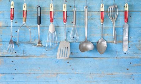 utensili da cucina d'epoca sulla parete rustica blu, copia spazio libero