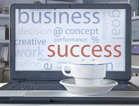 business conncept on laptop screen, tag cloud and a cup of coffee Stock Photo