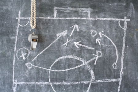 football or tactics blackboard with diagram and whistle of a trainer or referee
