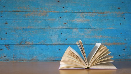 open book on blue grungy background