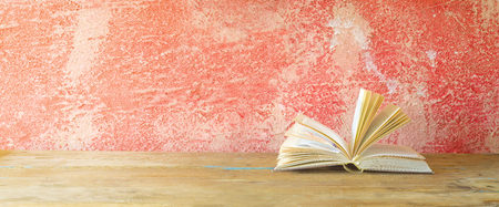 bibliomania: open book on red grungy background, good copy space Stock Photo