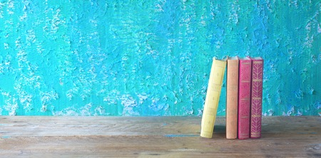 bibliomania: row of books on green grungy background, good copy space Stock Photo