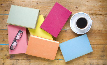 cofffee: multicolored books,cup of cofffee, specs,  flat lay Stock Photo