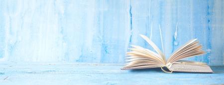 Geopend boek op blauwe grungy achtergrond, panoramische, goede kopie ruimte