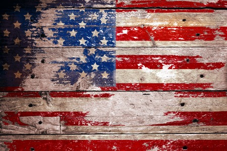 peeled off: damaged grungy USA flag, stars and stripes on weatherd wooden planks