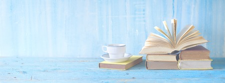 open book, cup of coffee on blue grungy background, panoramic, copy space