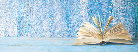 open book on blue grungy background, panoramic, good copy space