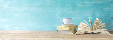 opened book, cup of coffee on grungy background, panoramic, copy space Foto de archivo