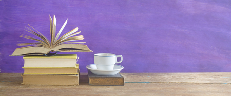 bibliomania: open book and cup of coffee on purple background,free copy space