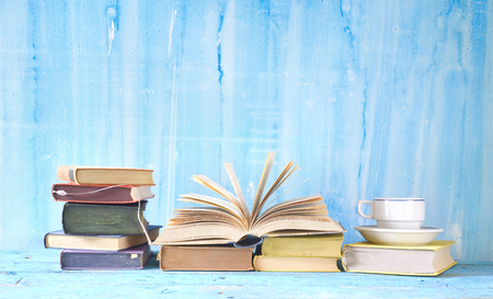 vintage books with one open book and coffee cup , free copy space