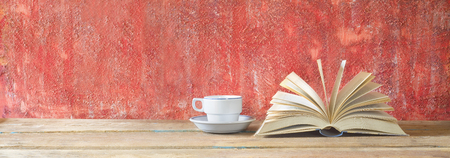 bibliomania: open book on red grungy background and cup of coffee, good copy space